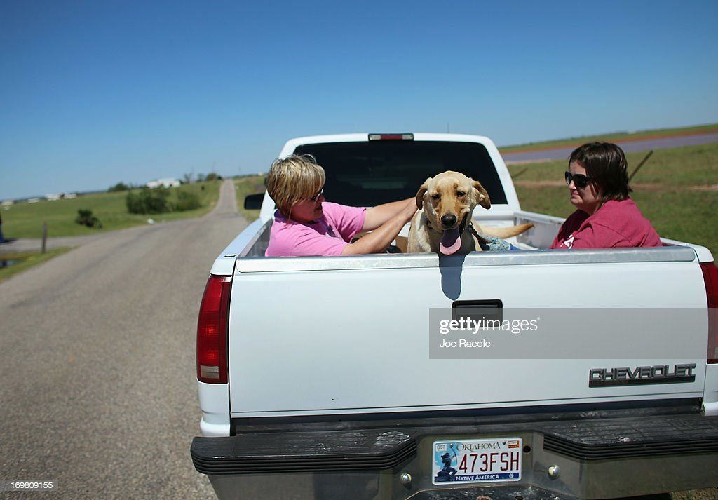 Conni Grulkey (L) and Heather Murray sit with a lost dog as they drive around searching for the owner after a tornado passed through the area on June 2, 2013 in El Reno, Oklahoma. The tornado ripped through the area friday killing at least 9 people injuring many and destroyed homes and buildings.