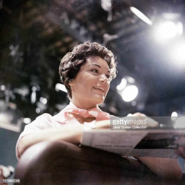 Connie Francis US singer wearing a pink neckscarf as she smiles with studio lights in the background circa 1965