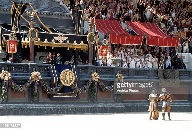 Connie Nielsen and Joaquin Phoenix looking with crowd out over the gladiatorial arena in a scene from the film 'Gladiator' 2000