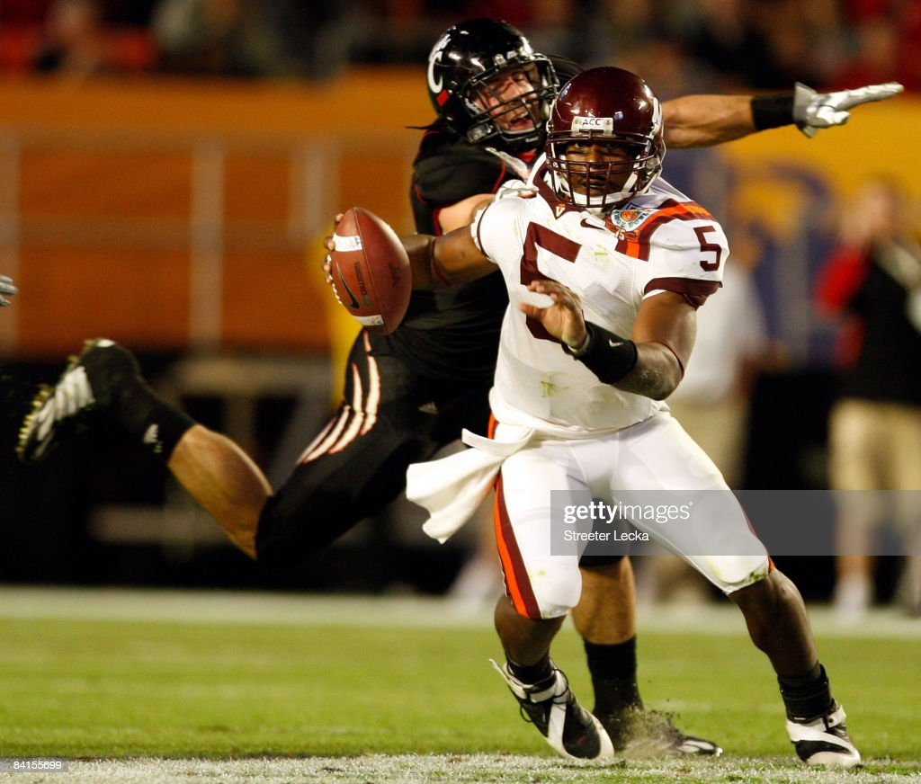 Connor Barwin of the Cincinnati Bearcats tries to tackle Tyrod Taylor of the Virginia Tech Hokies during the FedEx Orange Bowl at Dolphin Stadium on...