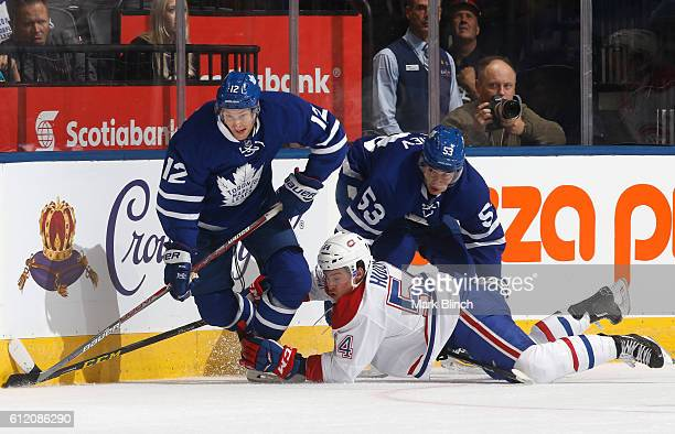 Connor Brown and teammate Rinat Valiev of the Toronto Maple Leafs battle for the puck with Charles Hudon of the Montreal Canadiens in the first...