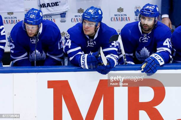 Connor Brown of the Toronto Maple Leafs Auston Matthews and Nazem Kadri sit on the bench against the Washington Capitals during overtime in Game Six...