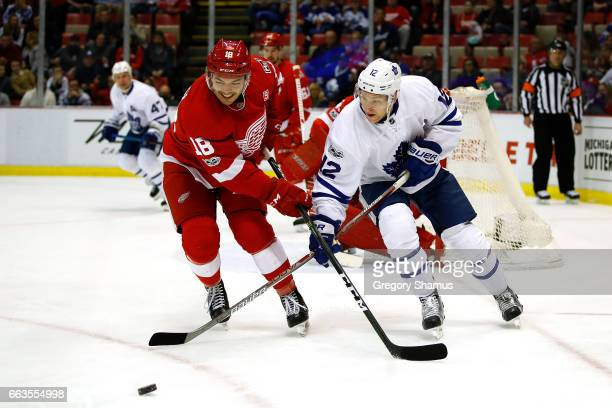Connor Brown of the Toronto Maple Leafs battles for the puck with Robbie Russo of the Detroit Red Wings during the first period at Joe Louis Arena on...