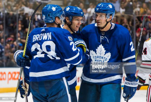 Connor Brown of the Toronto Maple Leafs celebrates his goal with teammates Nikita Zaitsev and Ron Hainsey against the Chicago Blackhawks during the...