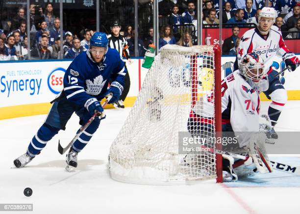 Connor Brown of the Toronto Maple Leafs comes around the net of Braden Holtby of the Washington Capitals as teammate John Carlson follows the play...