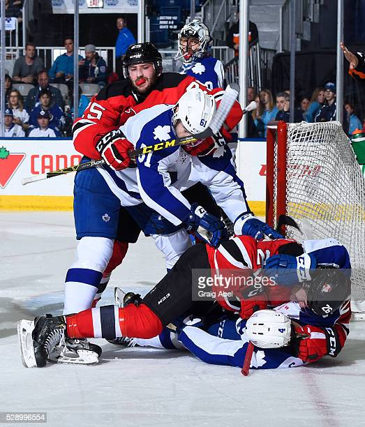 Connor Carrick and Rinat Valiev of the Toronto Marlies mixes it up with Ben Thomson and Nick Lappin of the Albany Devils during 2nd round AHL playoff...
