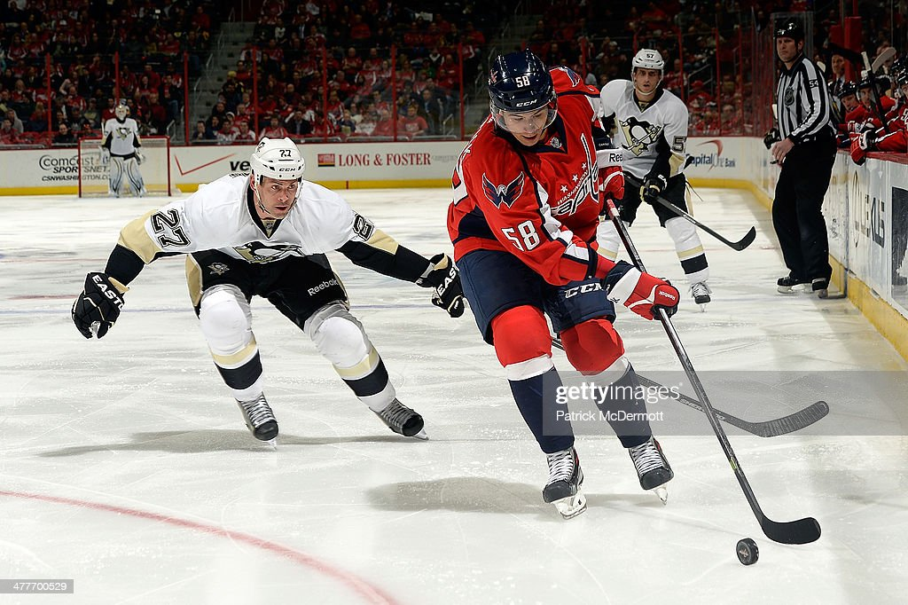 <a gi-track='captionPersonalityLinkClicked' href=/galleries/search?phrase=Connor+Carrick&family=editorial&specificpeople=9491429 ng-click='$event.stopPropagation()'>Connor Carrick</a> #58 of the Washington Capitals moves the puck up ice in the third period against <a gi-track='captionPersonalityLinkClicked' href=/galleries/search?phrase=Craig+Adams&family=editorial&specificpeople=211144 ng-click='$event.stopPropagation()'>Craig Adams</a> #27 of the Pittsburgh Penguins during an NHL game at Verizon Center on March 10, 2014 in Washington, DC.