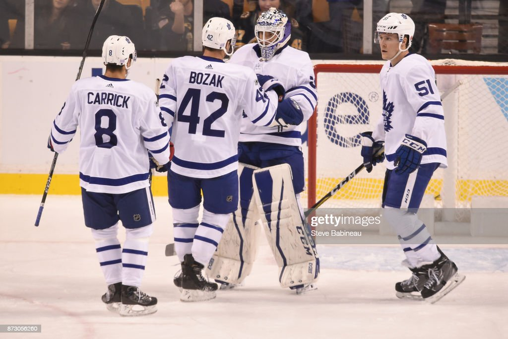 Connor Carrick #8, Tyler Bozak #42, Curtis McElhinney #35 and Jake Gardiner #51 of the Toronto Maple Leafs celebrate a win against the Boston Bruins at the TD Garden on November 11, 2017 in Boston, Massachusetts.