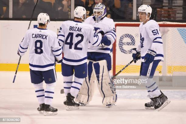 Connor Carrick Tyler Bozak Curtis McElhinney and Jake Gardiner of the Toronto Maple Leafs celebrate a win against the Boston Bruins at the TD Garden...