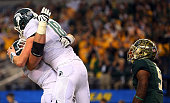 Connor Cook of the Michigan State Spartans and Brian Allen of the Michigan State Spartans celebrate after a touchdown pass to Keith Mumphery of the...