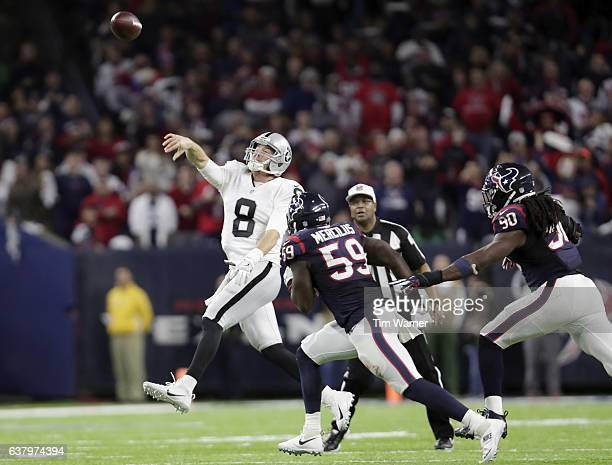 Connor Cook of the Oakland Raiders gets a pass away under pressure by Whitney Mercilus of the Houston Texans and Jadeveon Clowney at NRG Stadium on...