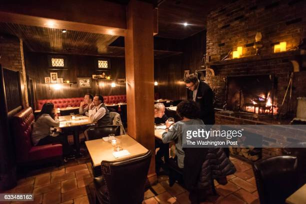 Connor Gropp serves customers near the fireplace in the dining room Iron Gate restaurant has a new Family Table menu that offers a fixed menu at a...