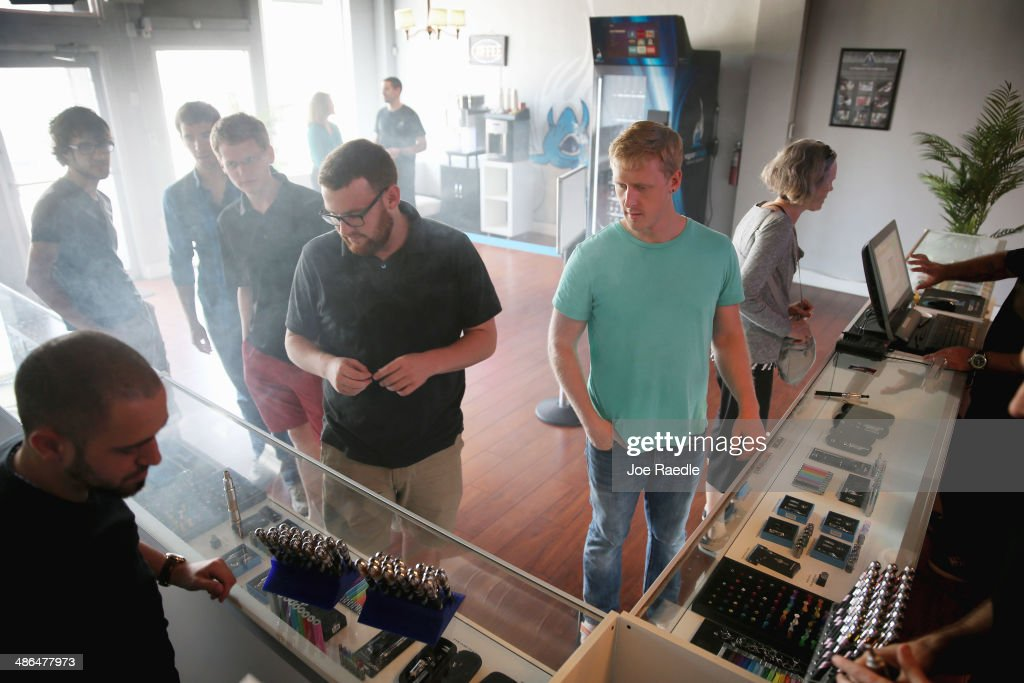 Connor Hailey (L) and Jon Lusher (R) shop for electronic cigarettes at the Vapor Shark store on April 24, 2014 in Miami, Florida. Brandon Leidel, CEO, Director of Operations Vapor Shark, said he welcomes the annoucement by the Food and Drug Administration that they are proposing the first federal regulations on electronic cigarettes, which would ban sales of the popular devices to anyone under 18 and require makers to gain FDA approval for their products.