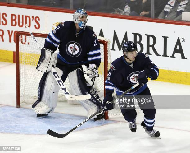 Connor Hellebuyck and Jacob Trouba of the Winnipeg Jets follow the puck during NHL action against the Calgary Flames during NHL action on March 11...