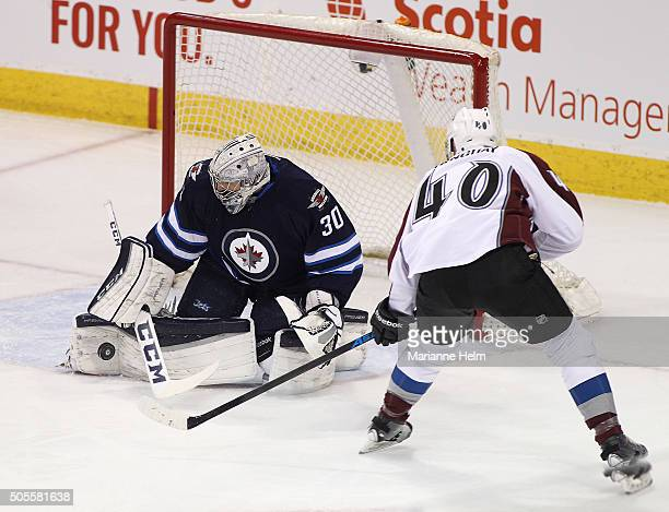 Connor Hellebuyck of the Winnipeg Jets blocks a shot on goal by Alex Tanguay of the Colorado Avalanche in first period action in an NHL game at the...