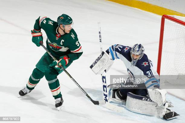 Connor Hellebuyck of the Winnipeg Jets defends his goal against Mikko Koivu of the Minnesota Wild during the game at the Xcel Energy Center on...