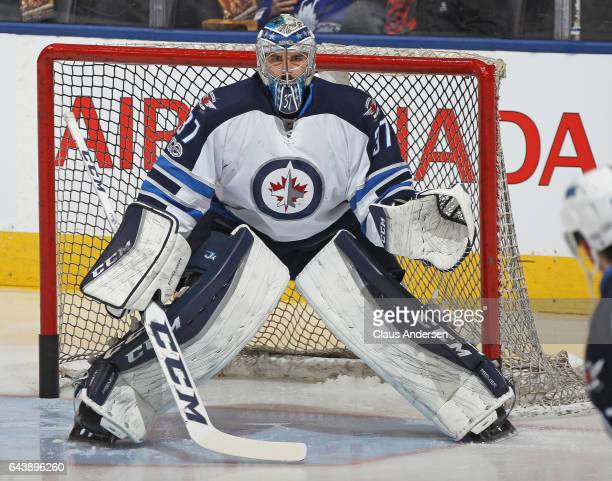 Connor Hellebuyck of the Winnipeg Jets gets set to face a shot during warmup prior to playing against the Toronto Maple Leafs in an NHL game at Air...