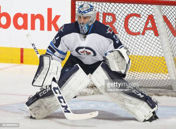 Connor Hellebuyck of the Winnipeg Jets gets set to face a shot during the warmup prior to play against the Toronto Maple Leafs in an NHL game at Air...