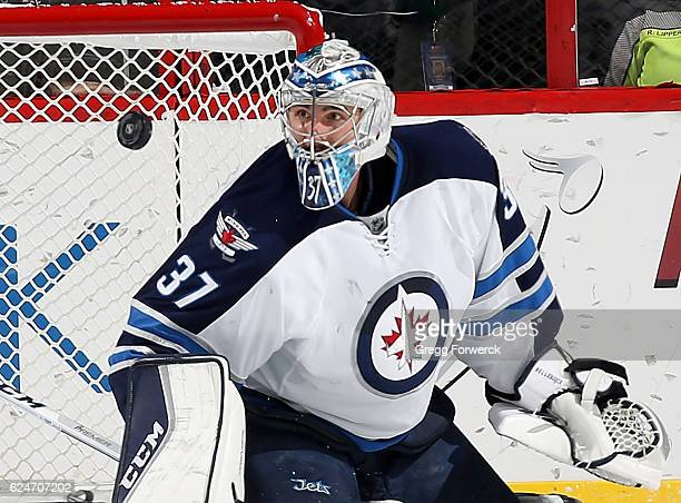 Connor Hellebuyck of the Winnipeg Jets goes down in the crease and keeps his eye on the puck during an NHL game against the Carolina Hurricanes on...