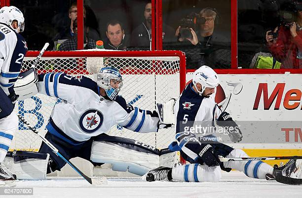 Connor Hellebuyck of the Winnipeg Jets goes down in the crease to protect the net as teammate Mark Stuart defends during an NHL game against the...