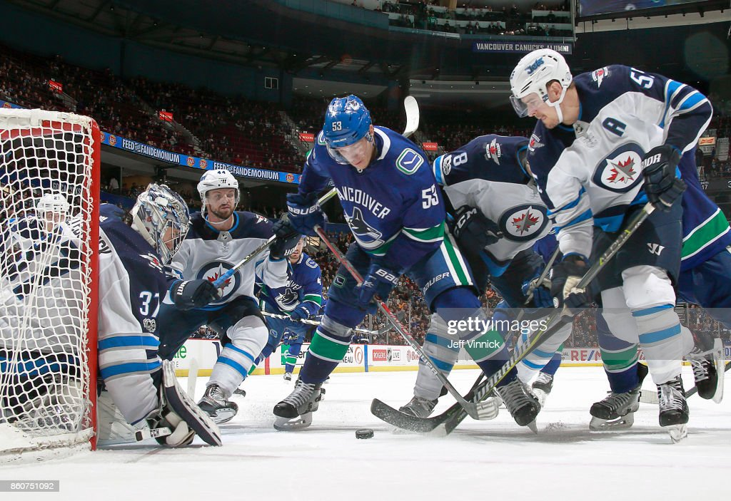 Connor Hellebuyck #37 of the Winnipeg Jets looks on as Bo Horvat #53 of the Vancouver Canucks and Mark Scheifele #55 of the Winnipeg Jets battle for the puck during their NHL game against the Winnipeg Jets at Rogers Arena October 12, 2017 in Vancouver, British Columbia, Canada. The Winnipeg Jets won 4-2.