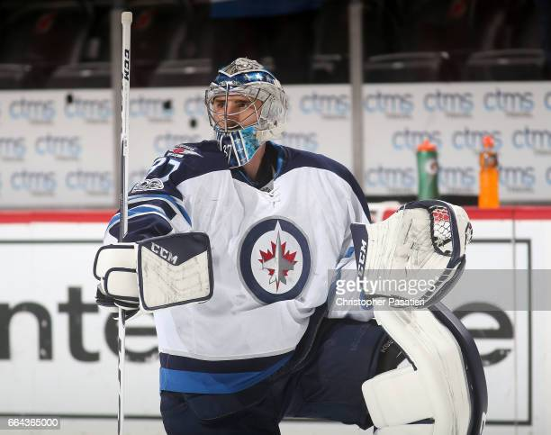 Connor Hellebuyck of the Winnipeg Jets looks on during warm ups prior to the game against the New Jersey Devils on March 28 2017 at the Prudential...