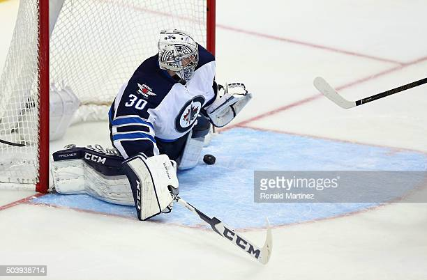 Connor Hellebuyck of the Winnipeg Jets makes a save against the Dallas Stars in the third period at American Airlines Center on January 7 2016 in...