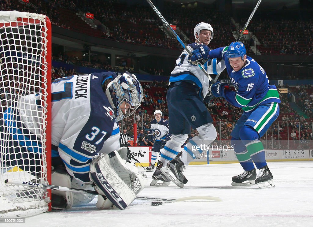 Connor Hellebuyck #37 of the Winnipeg Jets makes a save as Tyler Myers #57 of the Winnipeg Jets checks Derek Dorsett #15 of the Vancouver Canucks during their NHL game at Rogers Arena October 12, 2017 in Vancouver, British Columbia, Canada. The Winnipeg Jets won 4-2.