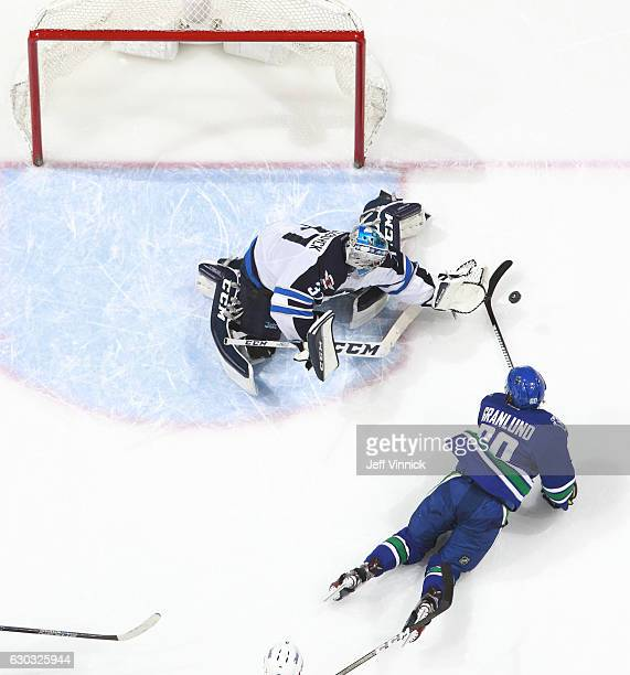 Connor Hellebuyck of the Winnipeg Jets makes a save on Markus Granlund of the Vancouver Canucks during their NHL game at Rogers Arena December 20...