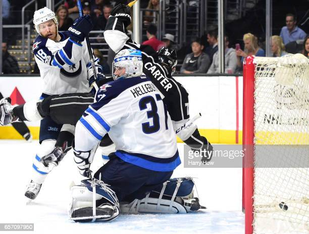 Connor Hellebuyck of the Winnipeg Jets reacts to a goal from Jake Muzzin of the Los Angeles Kings as Jeff Carter and Bryan Little stand in front of...