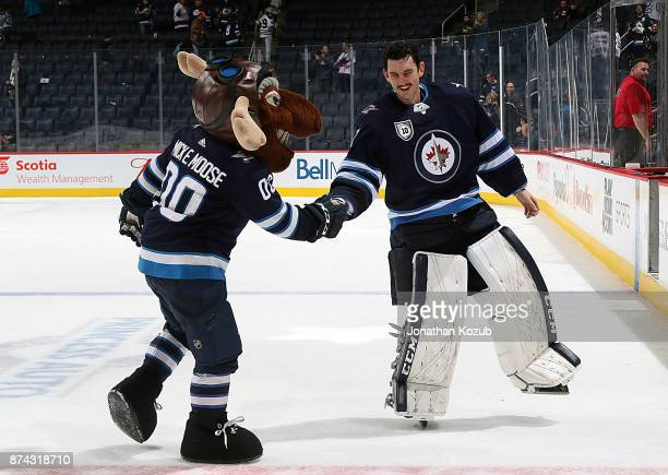 Connor Hellebuyck of the Winnipeg Jets shares a laugh with team mascot Mick E Moose following a 41 victory over the Arizona Coyotes at the Bell MTS...