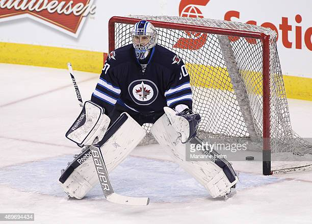 Connor Hellebuyck of the Winnipeg Jets warms up on the ice prior to an NHL game against the Calgary Flames at the MTS Centre on April 11 2015 in...