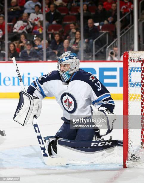 Connor Hellebuyck of the Winnipeg Jets watches the game action as he tends goal during the second period against the New Jersey Devils on March 28...