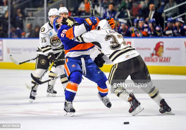 Connor Jones of the Bridgeport Sound Tigers gets hit by Hubert Labrie of the Hershey Bears during a game at the Webster Bank Arena on February 19...