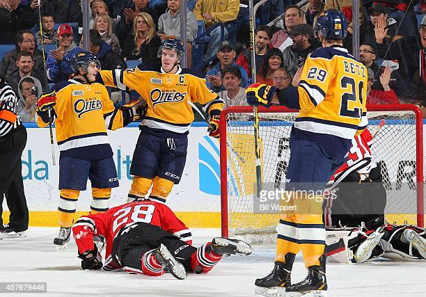 Connor McDavid and Alex Debrincat of the Erie Otters celebrate a first period goal near Aaron Haydon of the Niagara IceDogs in an OHL hockey game at...