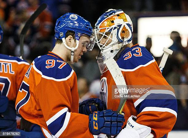 Connor McDavid and goaltender Cam Talbot of the Edmonton Oilers celebrate their victory against the Vancouver Canucks on April 6 2016 at Rexall Place...