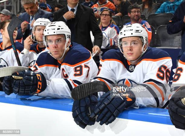 Connor McDavid and Kailer Yamamoto of the Edmonton Oilers sit on the bench prior to the preseason game against the Carolina Hurricanes on September...