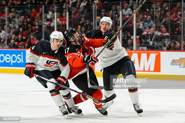 Connor McDavid of Team Canada gets crushed between Will Butcher of Team United States and teammate Ryan Collins in a preliminary round game during...