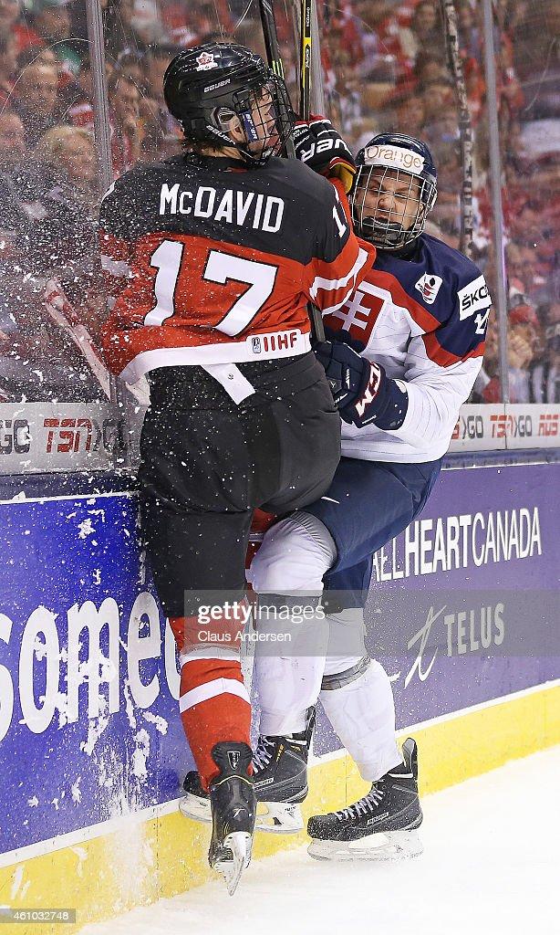 Connor McDavid of Team Canada slams into Erik Cernak of Team Slovakia during a semifinal game in the 2015 IIHF World Junior Hockey Championship at...