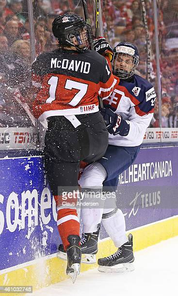 Connor McDavid of Team Canada slams into Erik Cernak of Team Slovakia during a semifinal game in the 2015 IIHF World Junior Hockey Championship at...
