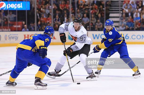Connor McDavid of Team North America stickhandles the puck against Anton Stralman and Marcus Kruger of Team Sweden during the World Cup of Hockey...