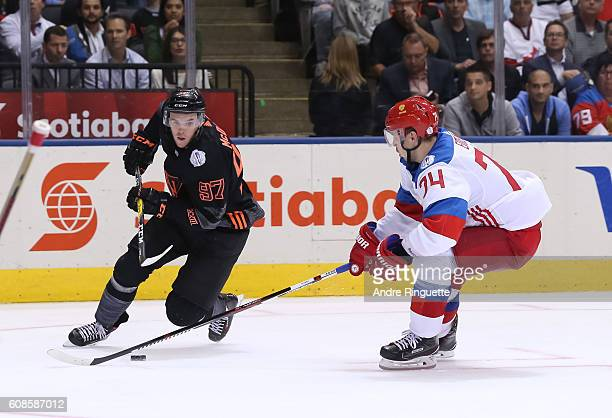 Connor McDavid of Team North America stickhandles the puck away from Alexei Emelin of Team Russia during the World Cup of Hockey 2016 at Air Canada...