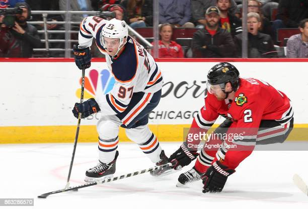 Connor McDavid of the Edmonton Oilers and Duncan Keith of the Chicago Blackhawks battle for the puck in overtime at the United Center on October 19...