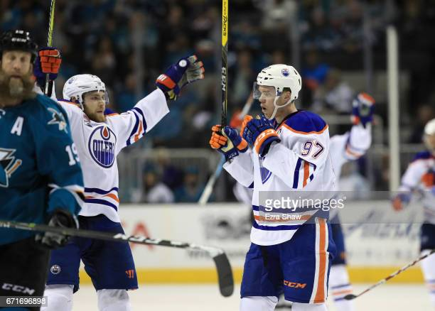 Connor McDavid of the Edmonton Oilers and Leon Draisaitl celebrate next to Joe Thornton of the San Jose Sharks after McDavid scored an empty net goal...