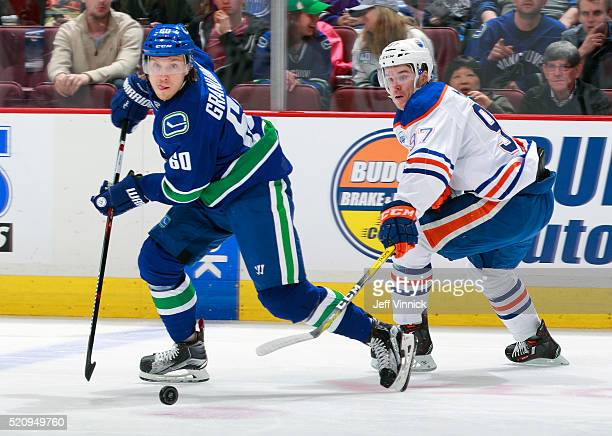 Connor McDavid of the Edmonton Oilers and Markus Granlund of the Vancouver Canucks watch a loose puck during their NHL game at Rogers Arena April 9...
