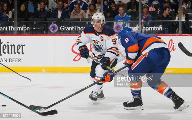 Connor McDavid of the Edmonton Oilers and Ryan Pulock of the New York Islanders chase a loose puck during the second period at Barclays Center on...