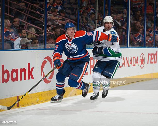 Connor McDavid of the Edmonton Oilers battles for the puck against Dan Hamhuis the Vancouver Canucks on October 1 2015 at Rexall Place in Edmonton...