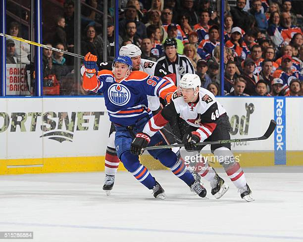Connor McDavid of the Edmonton Oilers battles for the puck against Jordan Martinook of the Arizona Coyotes on March 12 2016 at Rexall Place in...