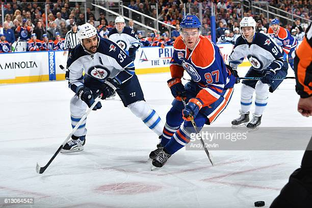 Connor McDavid of the Edmonton Oilers battles for the puck against Dustin Byfuglien of the Winnipeg Jets on October 6 2016 at Rogers Place in...