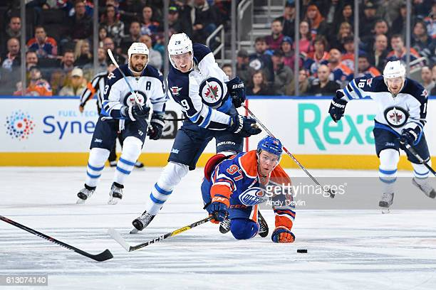 Connor McDavid of the Edmonton Oilers battles for the puck against Patrik Laine of the Winnipeg Jets on October 6 2016 at Rogers Place in Edmonton...
